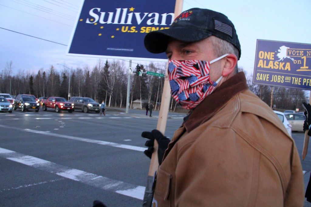 FILE - In this Nov. 2, 2020, file photo, Republican U.S. Sen. Dan Sullivan waves a sign at a busy intersection in Anchorage, Alaska. Sen. Sullivan on ...