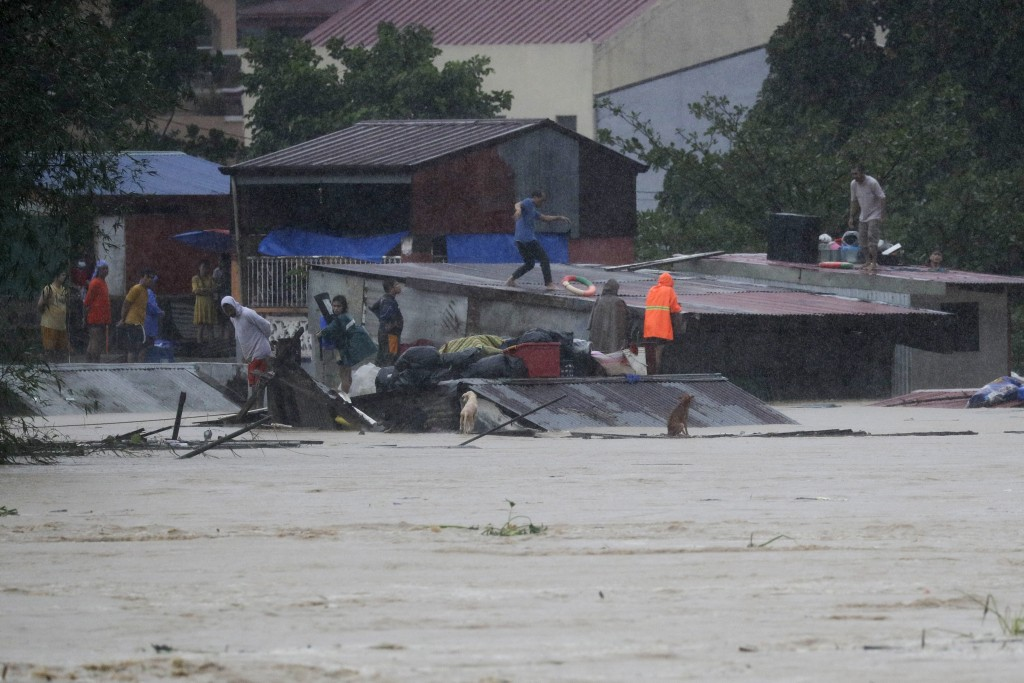 Residents trapped on their roofs prepare to evacuate as floods continue to rise in Marikina, Philippines due to Typhoon Vamco on Thursday, Nov. 12, 20...