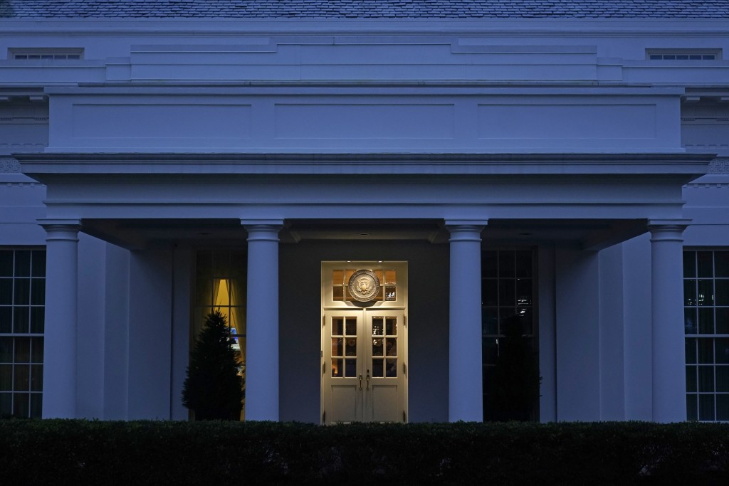 Lights shine on a door leading to the West Wing of the White House at dusk, Wednesday, Nov. 11, 2020, in Washington. (AP Photo/Patrick Semansky)