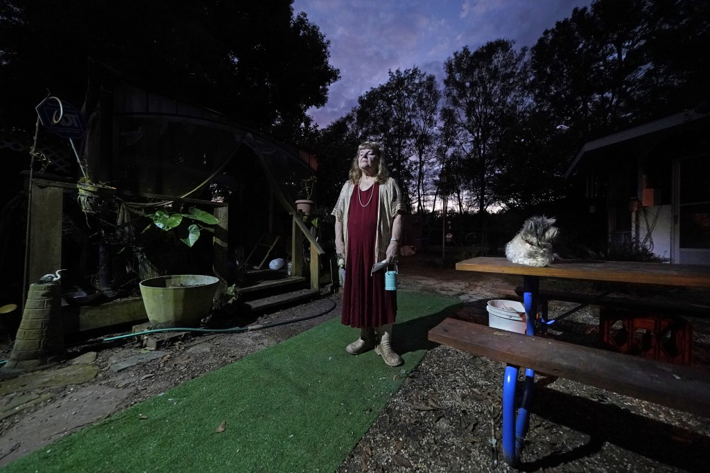 Joan Martin poses for a portrait with her Bichon Frise named Brigeet in the backyard of her home in Picayune, Miss., Wednesday, Nov. 11, 2020. When sh...