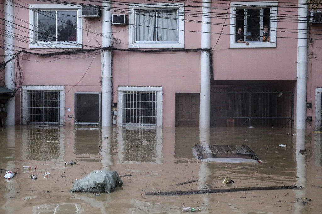 Residents look out from the window of their house as flood waters rise due to Typhoon Vamco in Providence village in Marikina City, east of Manila, Ph...