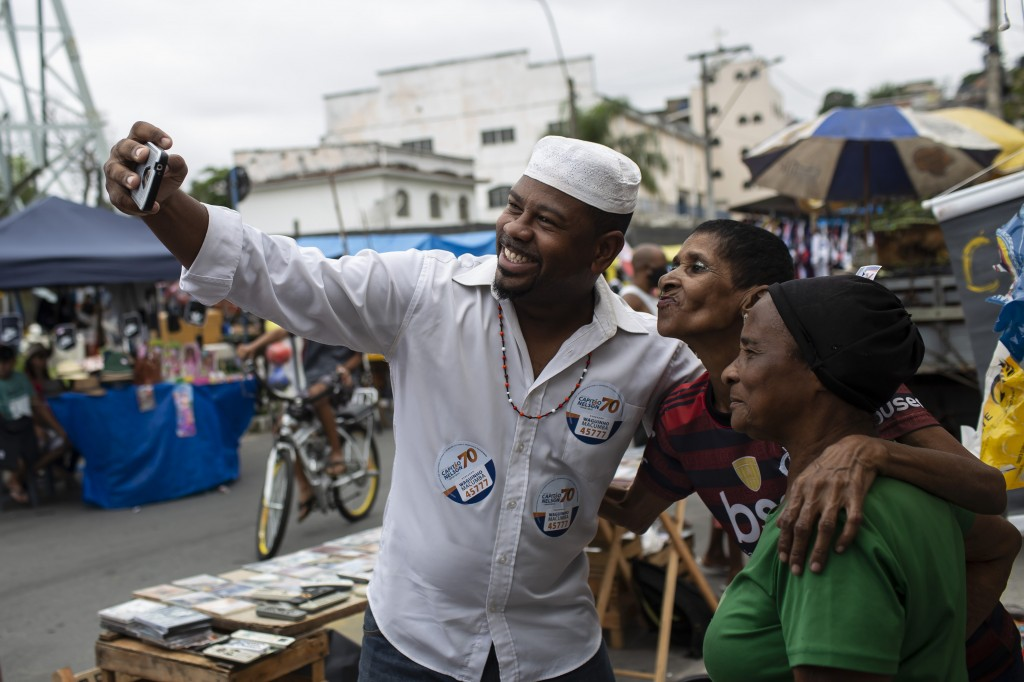 Wagner Luiz Abreu Machado, a priest from the Afro-Brazilian faith Umbanda who goes by Waguinho Macumba, takes a selfie with residents as he campaigns ...