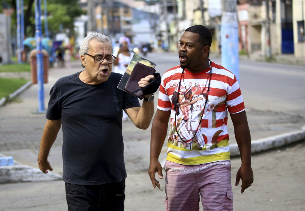 An Evangelical holds up a Bible as he shouts about the coming of Jesus and how Wagner Luiz Abreu Machado, a priest from the Afro-Brazilian faith Umban...
