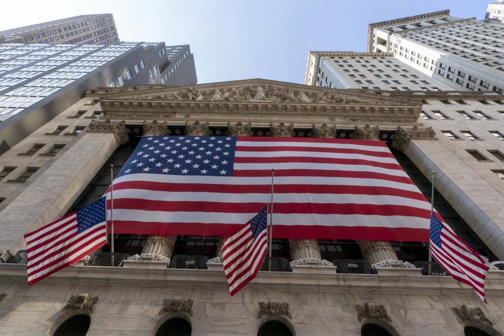 FILE - In this Monday, Sept. 21, 2020, file photo, a giant American Flag hangs on the New York Stock Exchange.  Wall Street is moving past the uncerta...