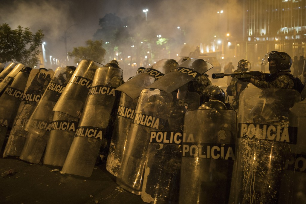 Police officers shield themselves from rocks thrown by protesters who were trying to march to Congress in a demonstration against the removal of Presi...