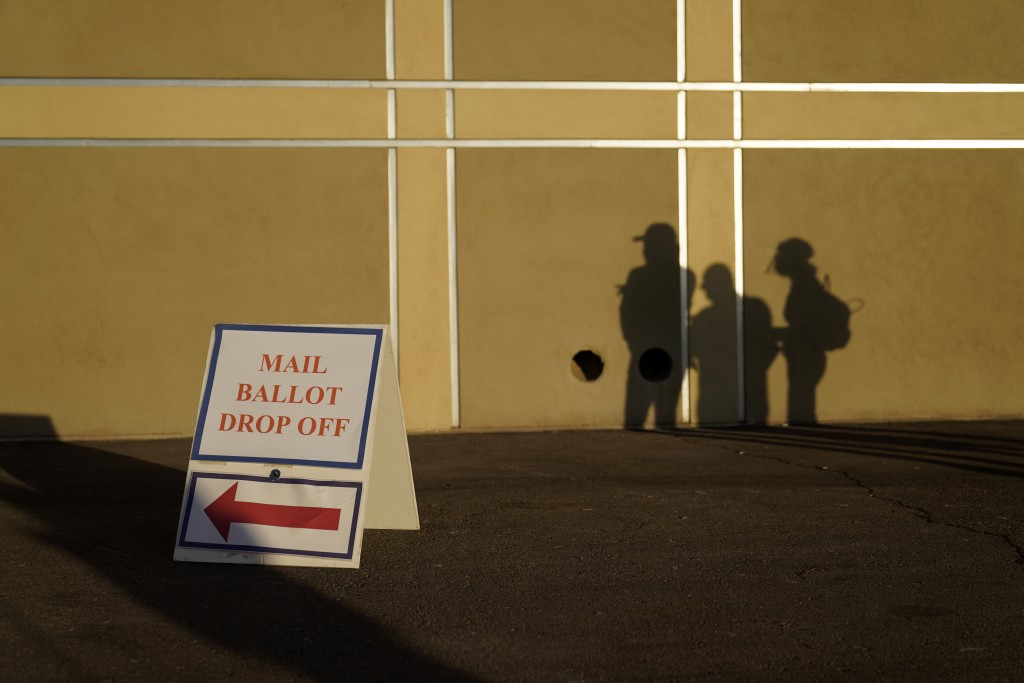 FILE - In this Nov. 3, 2020, file photo people wait outside of a polling place on Election Day in Las Vegas. Nevada election law stipulates that in or...