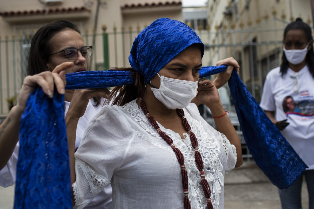 Candomble Priestess Claudia Lima gets help with her head covering as she prepares to campaign for a seat on the Rio de Janeiro City Council, represent...