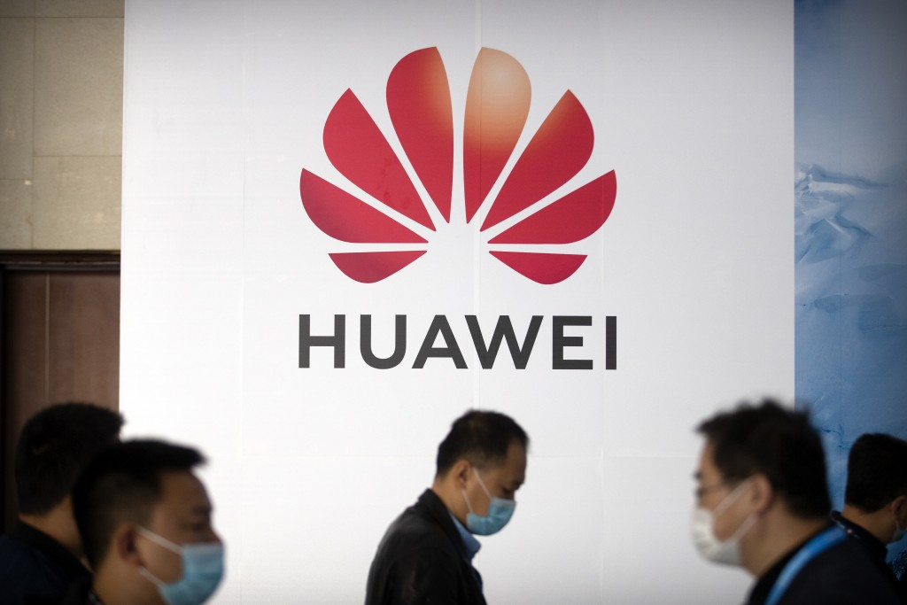 People walk past a billboard advertising Chinese tech company Huawei at the PT Expo in Beijing on Oct. 14, 2020. U.S. President Donald Trump has stepp...