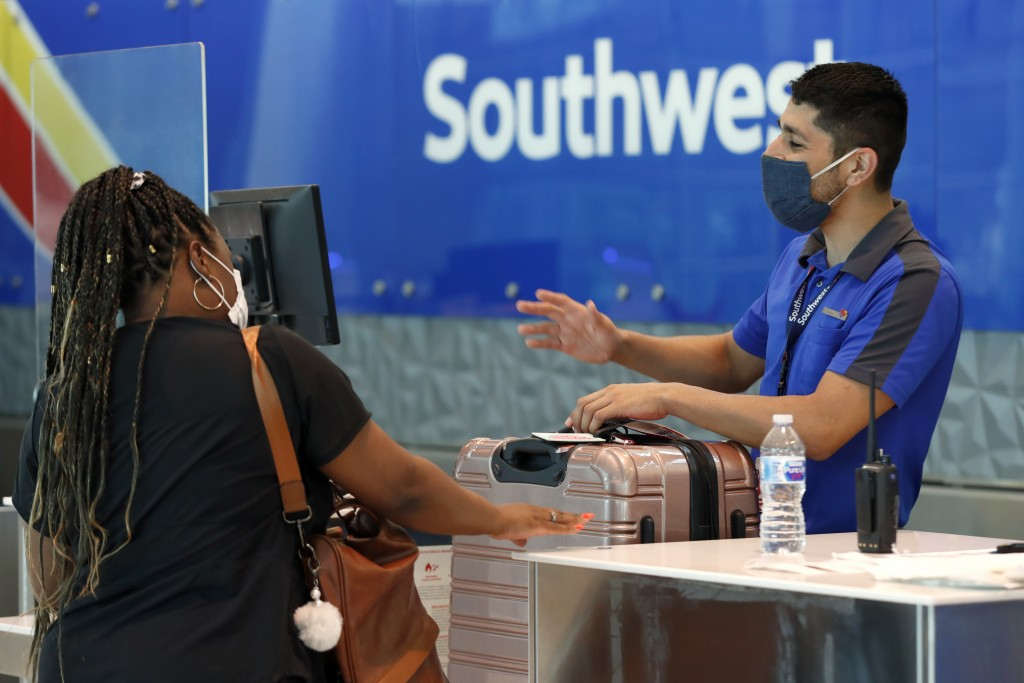 FILE - In this June 24, 2020 file photo, Southwest Airlines employee Oscar Gonzalez, right, assists a passenger at the ticket counter at Love Field in...