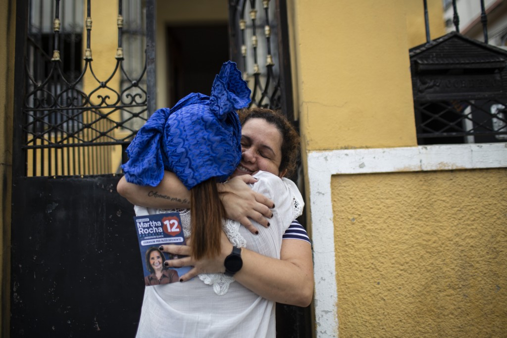Candomble Priestess Claudia Lima, back to camera, is hugged by a supporter as she campaigns for a seat on the Rio de Janeiro City Council, representin...