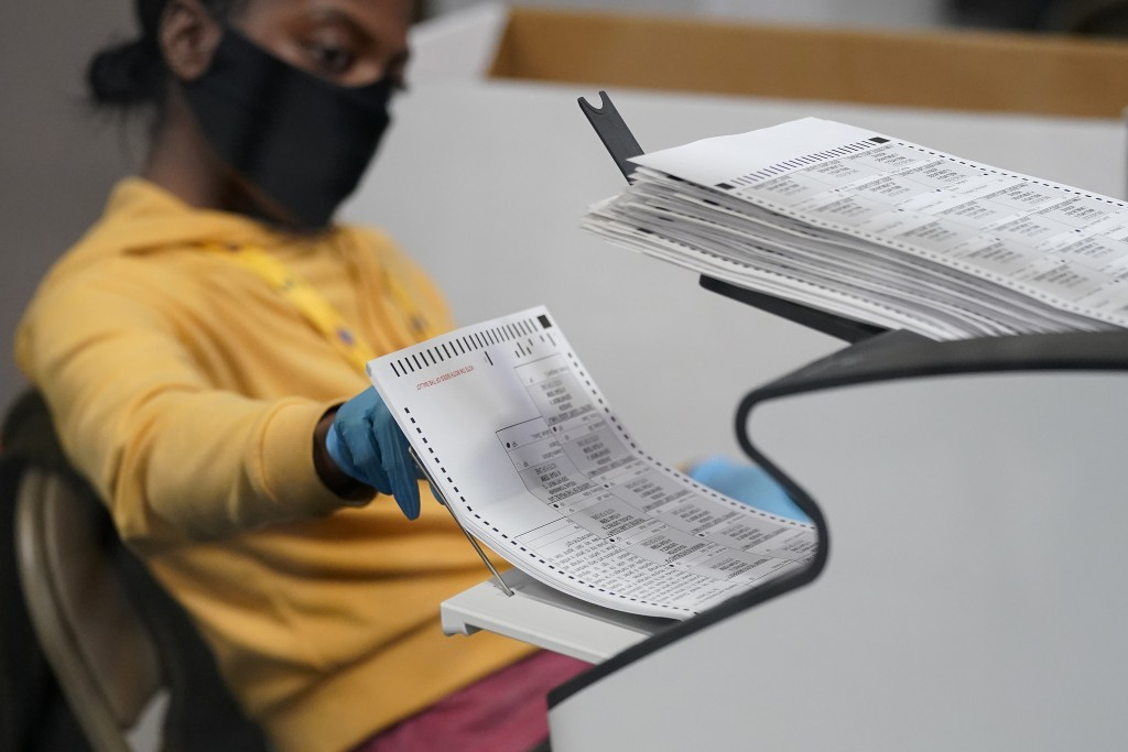 FILE - In this Nov. 5, 2020, file photo a county election worker scans mail-in ballots at a tabulating area at the Clark County Election Department in...
