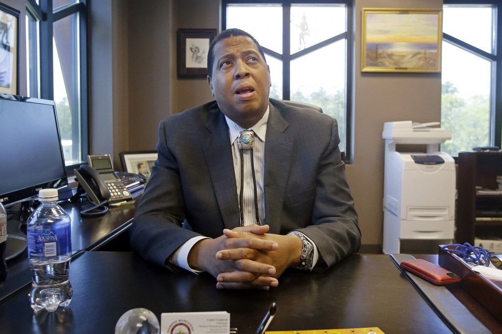 FILE - In this May 29, 2014 photo, Mashpee Wampanoag Tribe Chairman Cedric Cromwell sits behind his desk at the government center in Mashpee, Mass. Cr...