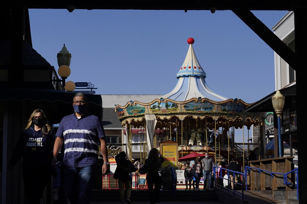 FILE - In this Nov. 12, 2020, file photo, people wear face masks while walking in front of the carousel at Pier 39 during the coronavirus outbreak in ...