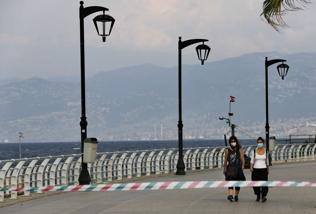 Two woman wear their masks while walking on the deserted corniche along the Mediterranean Sea, as the country began a two-week lockdown to limit the s...