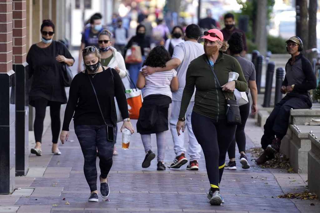 FILE - In this Nov. 6, 2020, file photo, people walk in downtown Evanston, Ill. With the coronavirus coming back with a vengeance across the country a...