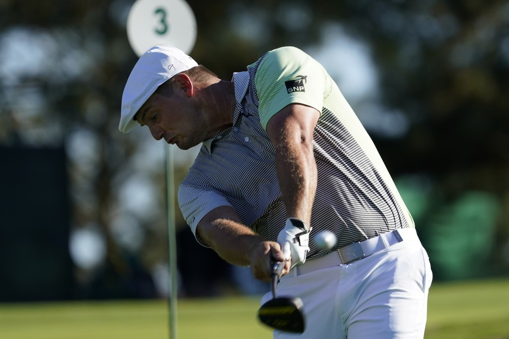Bryson DeChambeau hits his second tee shot after his first was lost off the third fairway during the second round of the Masters golf tournament Frida...