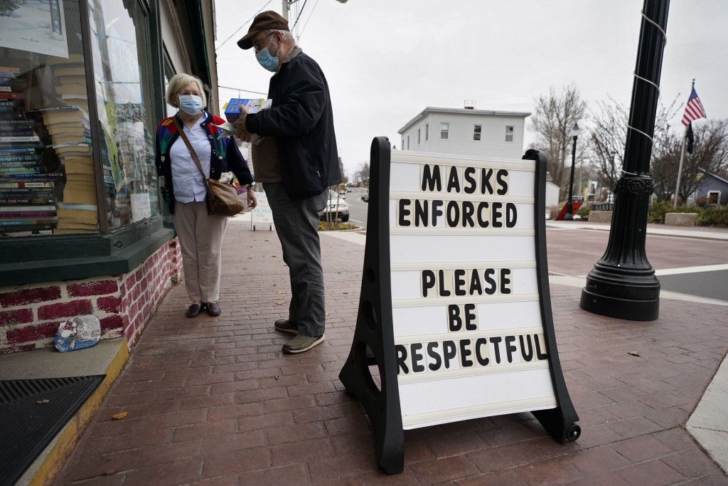 Shoppers comply with the mask regulations to help prevent the spread of the coronavirus at Bridgton Books, Friday, Nov. 13, 2020, in Bridgton, Maine. ...