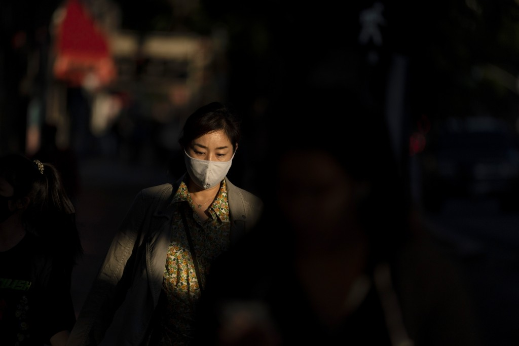 FILE - In this Nov. 12, 2020, file photo, a woman wearing a face mask walks along the street in the Hollywood section of Los Angeles. With the coronav...