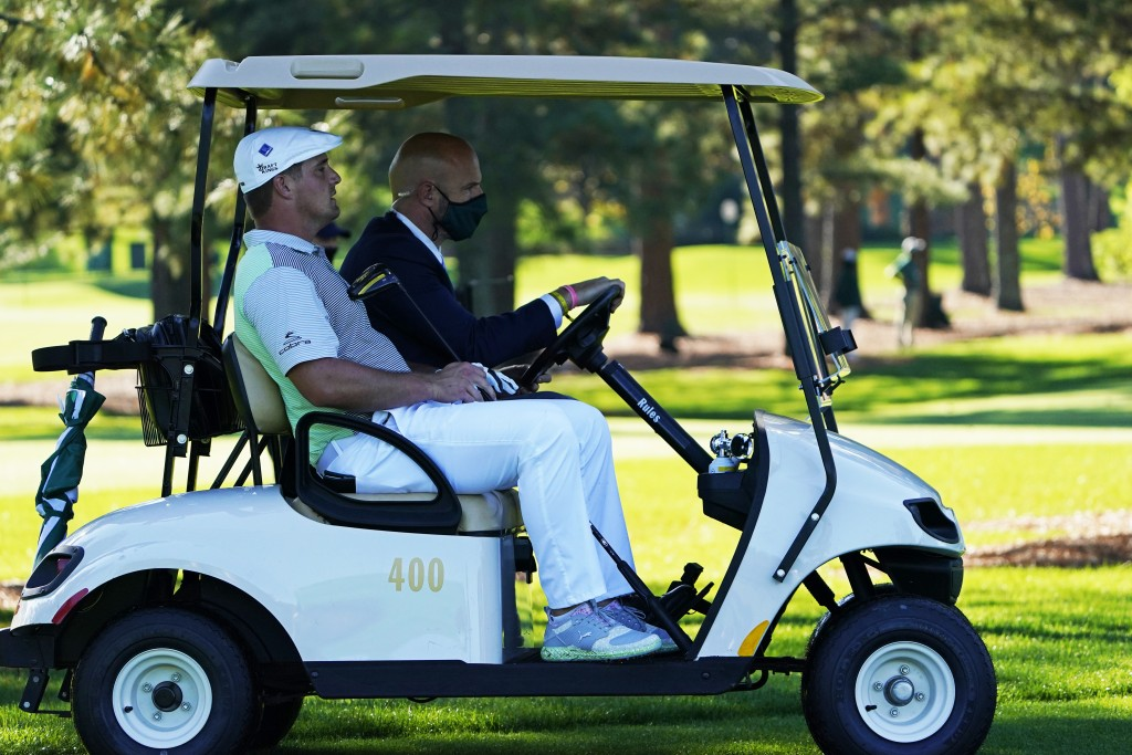 Bryson DeChambeau gets a ride back to the third tee box to hit again after his ball was lost during the second round of the Masters golf tournament Fr...