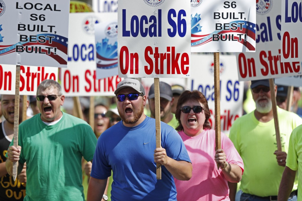 FILE - In this Saturday, July 25, 2020, file photo striking Bath Iron Works shipbuilders march in solidarity, in Bath, Maine. After a bitter two-month...