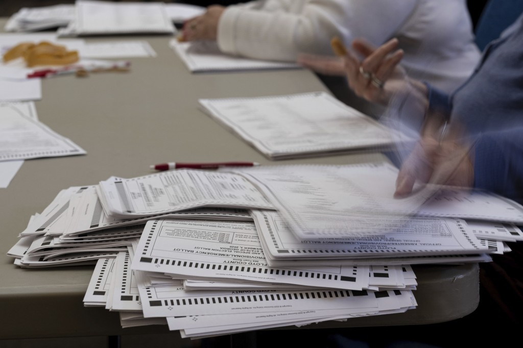 FILE - In this Nov. 13, 2020, file photo officials sort ballots during an audit at the Floyd County administration building in Rome, Ga. (AP Photo/Ben...