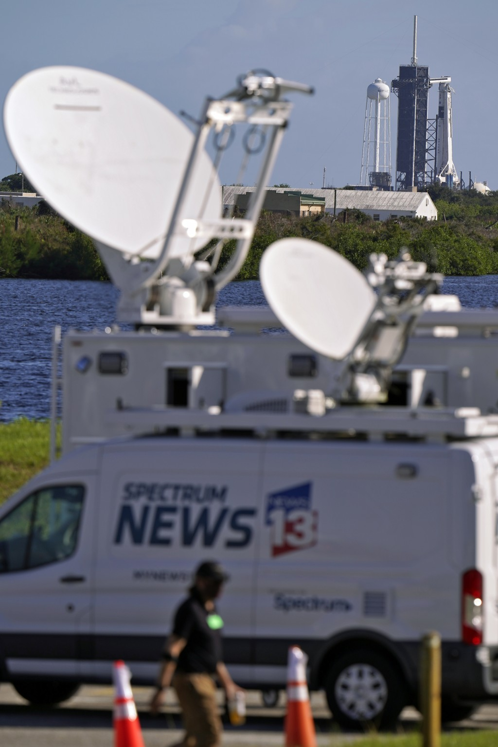 Members of the media set up equipment as a SpaceX Falcon 9 rocket, with the company's Crew Dragon capsule attached, sits on the launch pad at Launch C...