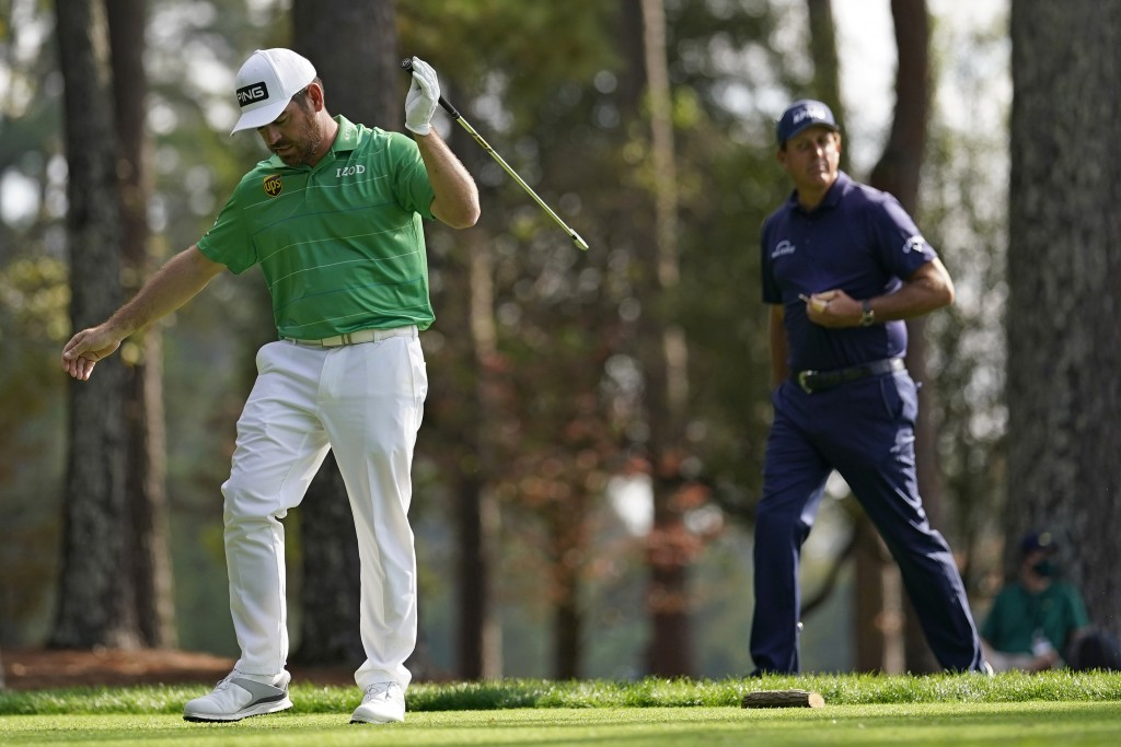 Phil Mickelson, right, watches as Louis Oosthuizen, of South Africa, reacts to his drive on the fourth tee during the third round of the Masters golf ...