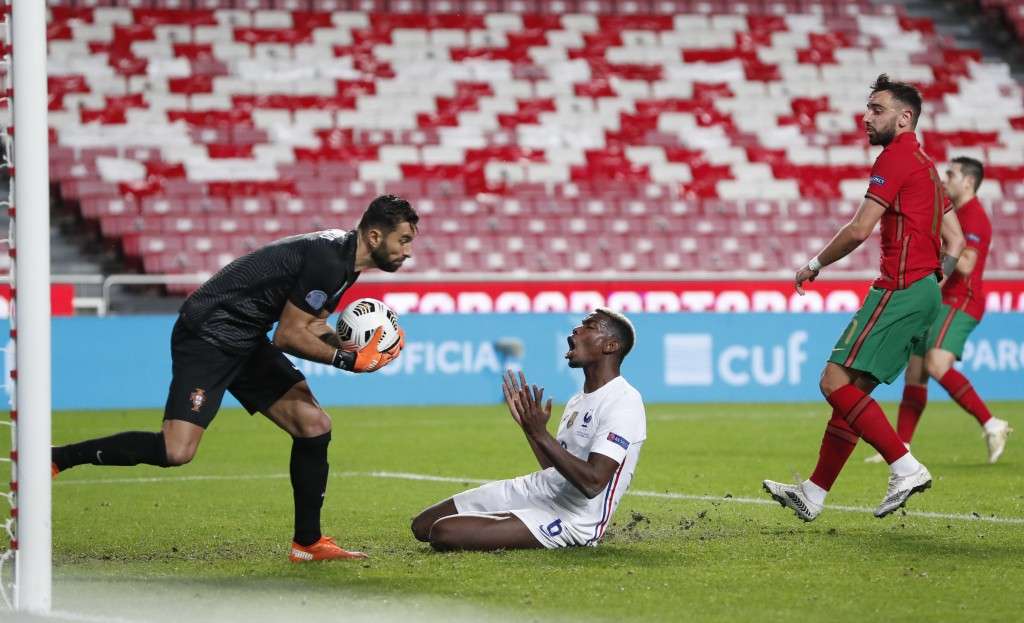 Portugal goalkeeper Rui Patricio collects the ball in front of France's Paul Pogba during the UEFA Nations League soccer match between Portugal and Fr...