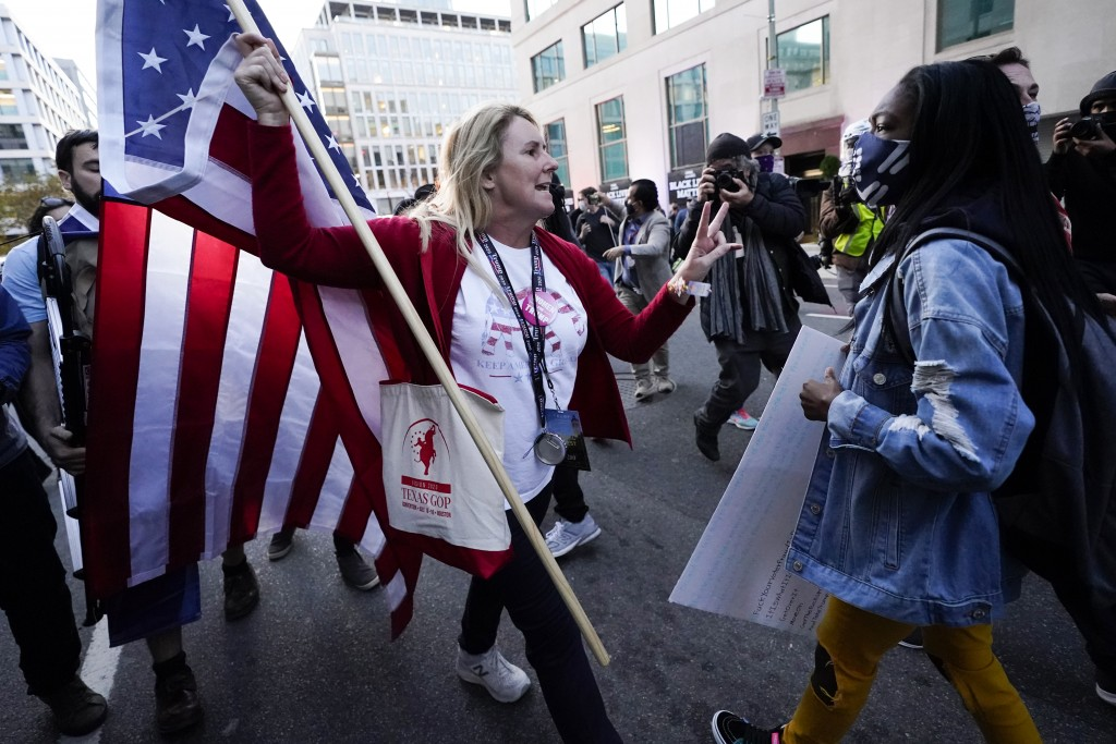 A woman gestures as she argues with a counter-protester after supporters of President Donald Trump held marches Saturday, Nov. 14, 2020, in Washington...