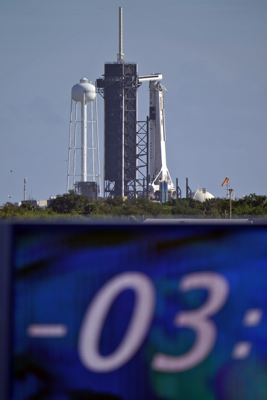 The countdown clock is stopped at a three-hour built in hold as a SpaceX Falcon 9 rocket, with the company's Crew Dragon capsule attached, sits on the...