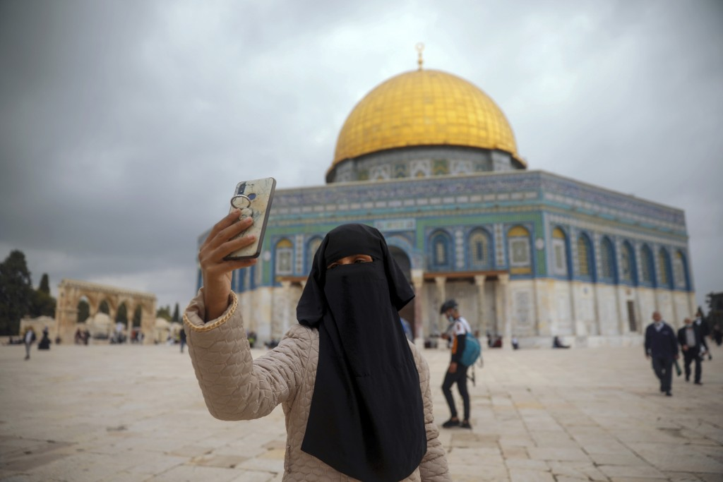 A Muslim woman takes a photo next to the Dome of the Rock Mosque in the Al Aqsa Mosque compound in Jerusalem's old city, Friday, Nov. 6, 2020. The Pal...