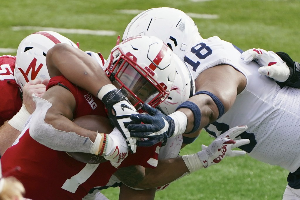 Nebraska wide receiver Wan'Dale Robinson (1) is tackled by Penn State defensive end Shaka Toney (18) during the second half of an NCAA college footbal...