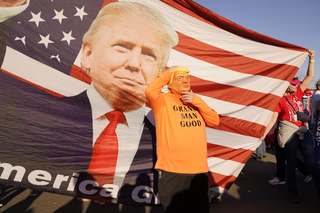A person in a President Donald Trump mask poses for photos in front of a background with Trump on it as supporters attend pro-Trump marches, Saturday ...