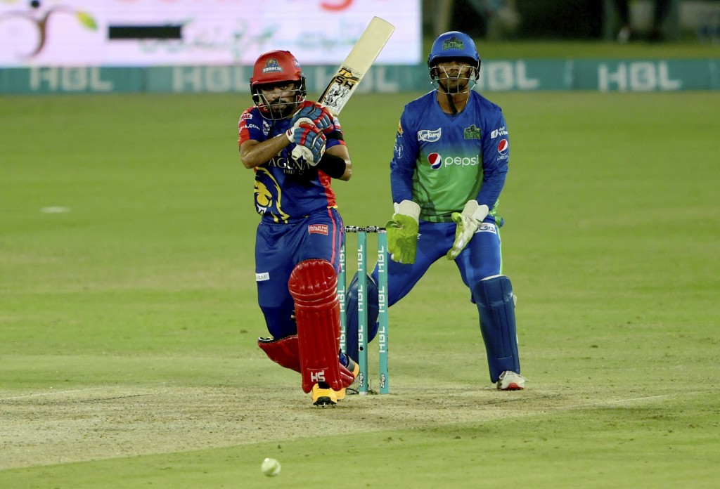Karachi Kings batsman Babar Azam, front, follows the ball after playing shot while Multan Sultans wicketkeeper Zeeshan Ashraf watches during the Pakis...