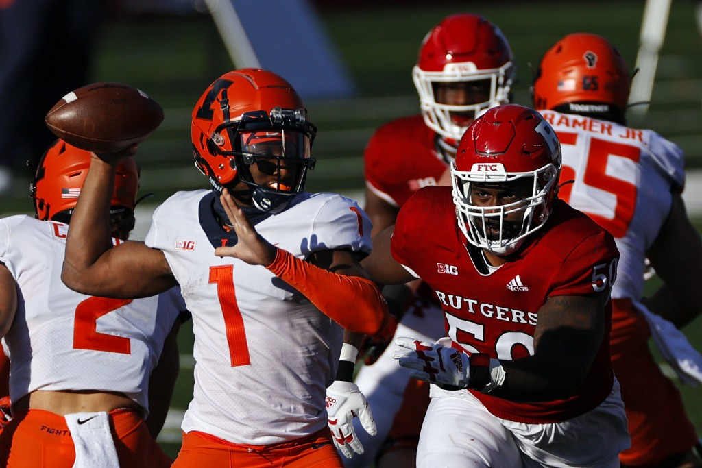 Illinois quarterback Isaiah Williams (1) passes under pressure from Rutgers defensive lineman Julius Turner during the first half of an NCAA college f...