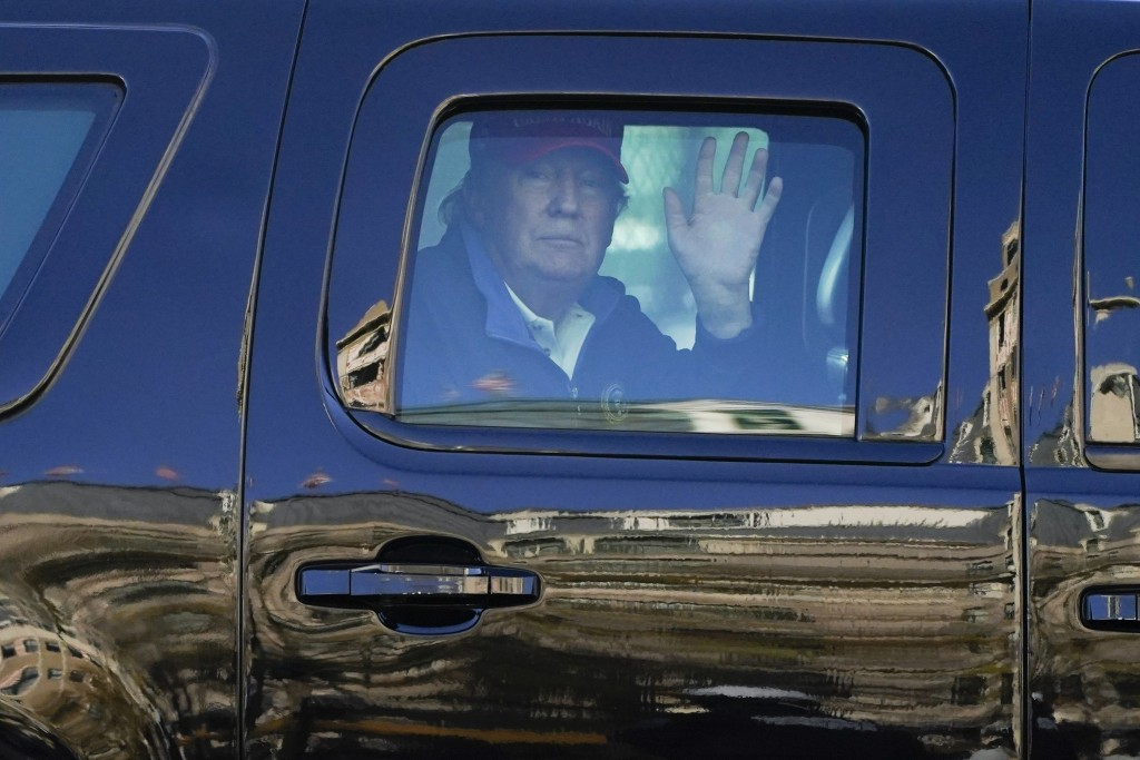 President Donald Trump waves to supporters from his motorcade as people gather for a march Saturday, Nov. 14, 2020, in Washington. (AP Photo/Julio Cor...