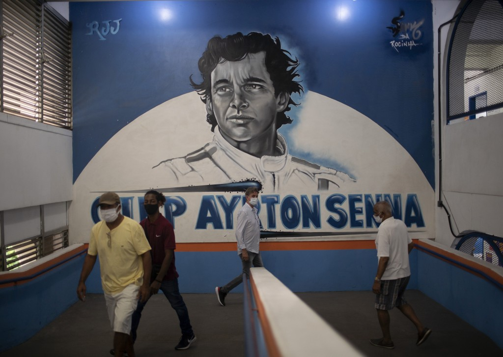 Residents enter a school where a mural of Brazil's late Formula One driver Ayrton Senna covers the wall during municipal elections, at a polling stati...