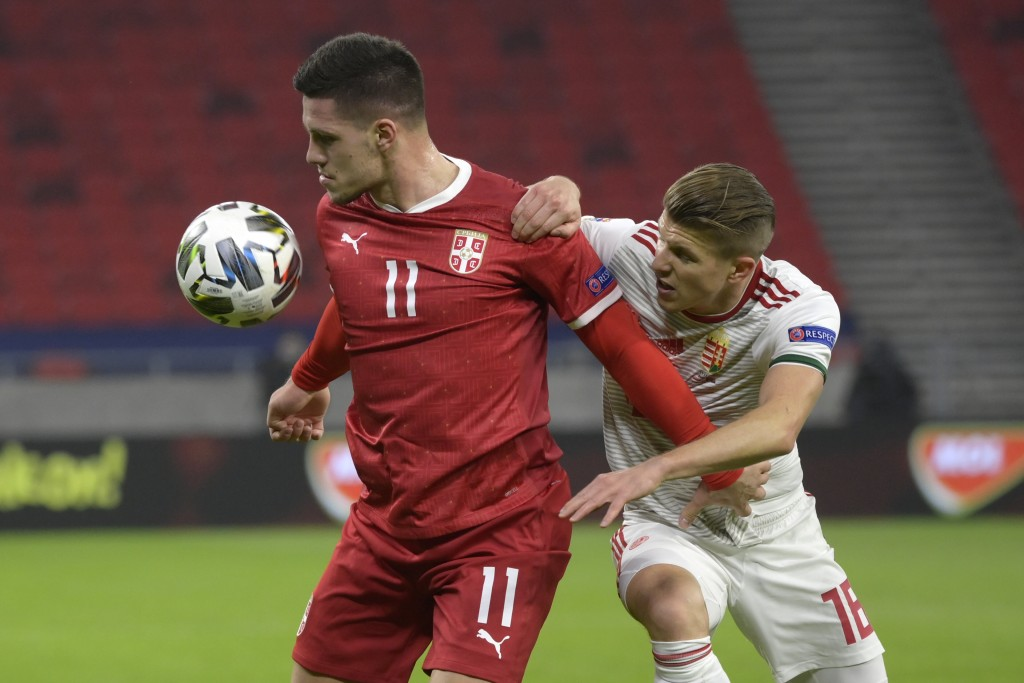 Luka Jovic of Serbia, left, is challenged by David Siger of Hungary for the ball during the UEFA Nations League soccer match Hungary vs. Serbia in Pus...