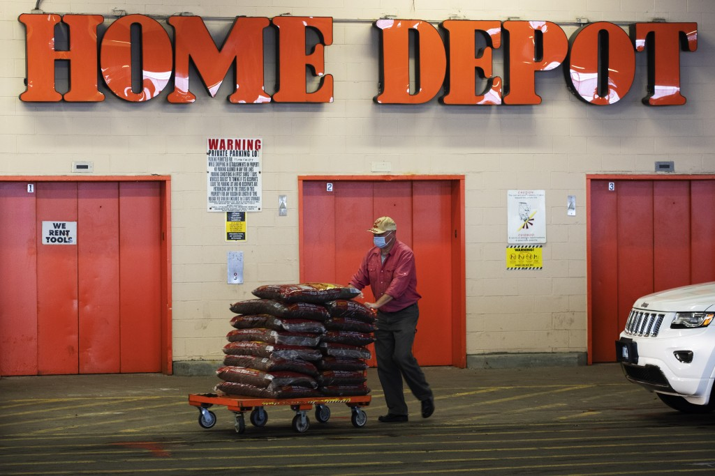 FILE - In this April 3, 2020 file photo, a Home Depot customer pushes a cart loaded with supplies in New York. Home Depot is buying HD Supply Co.,  a ...