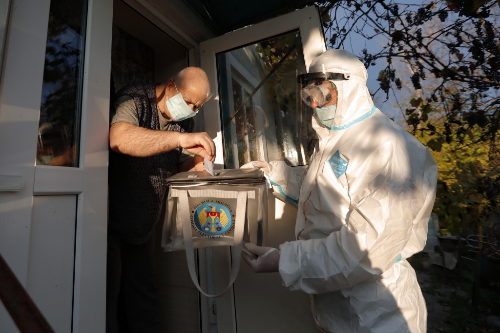 An election official wearing a biohazard suit, for protection against the COVID-19 infection, holds a mobile ballot box as a man casts his vote in the...