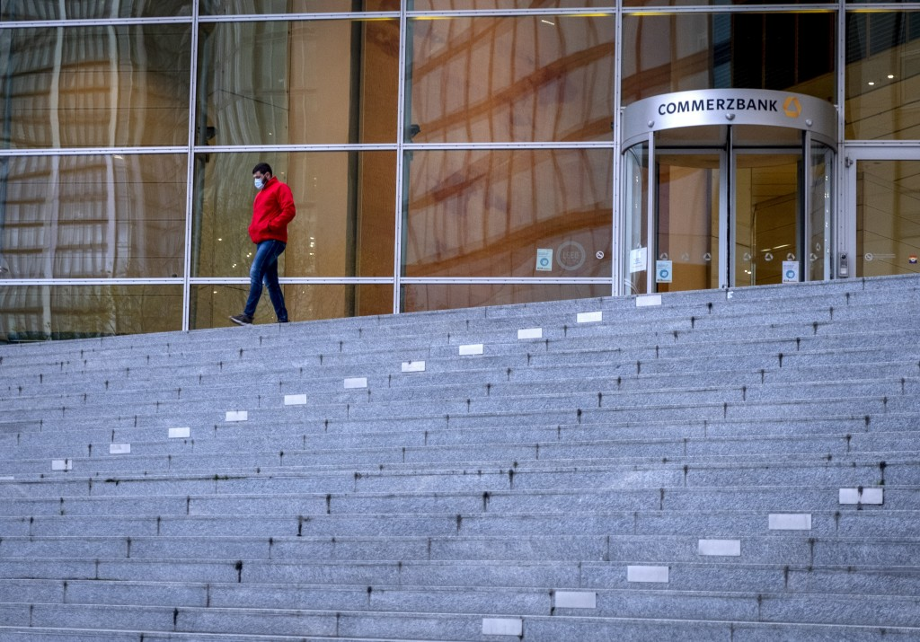 A man wearing a face mask walks down the stairs of the Commerzbank in the banking district of Frankfurt, Germany, Monday, Nov. 16, 2020. (AP Photo/Mic...