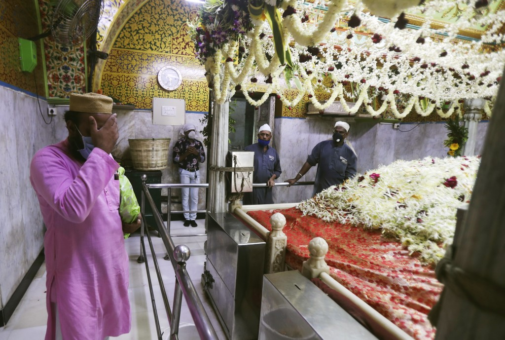 A man wearing mask offers prayers at the shrine of Makhdoom Ali Mahimi, an ancient Muslim scholar and saint in Mumbai, India, Monday, Nov. 16, 2020. R...