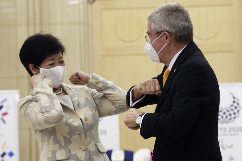 Tokyo Governor Yuriko Koike, left, greets International Olympic Committee President Thomas Bach before their meeting in Tokyo, Monday, Nov. 16, 2020. ...