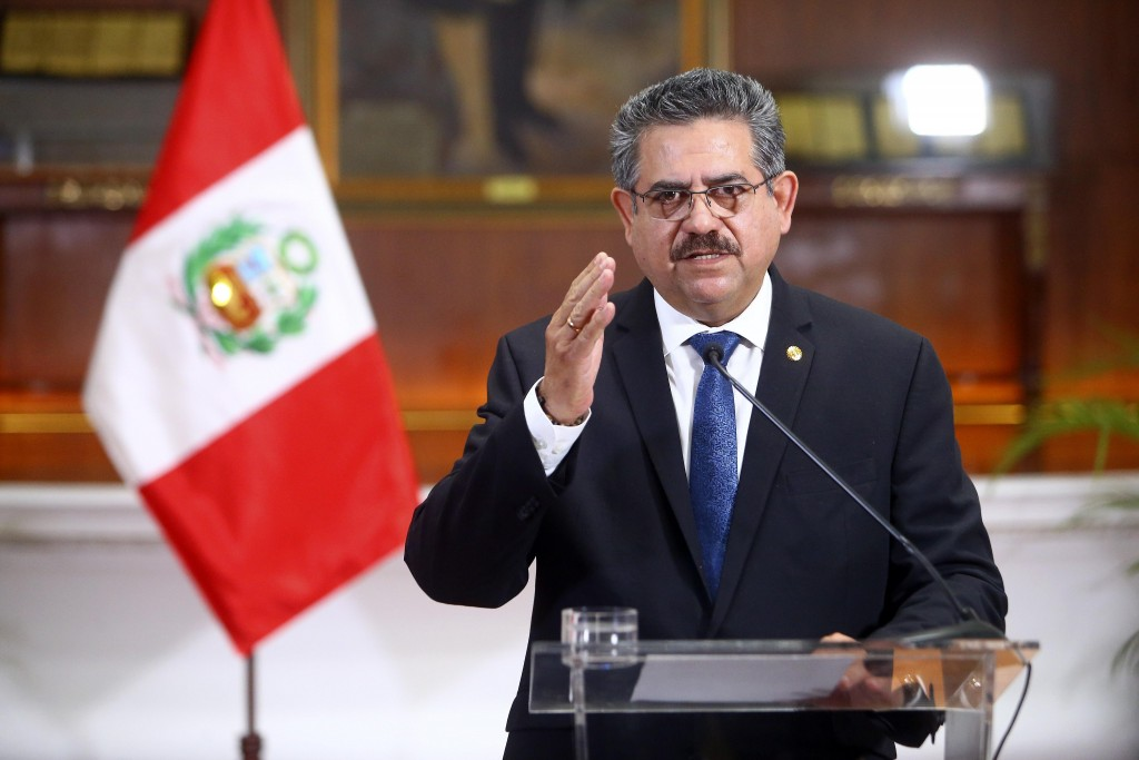 In this photo released by Peru's Presidential Palace, Peru's interim president Manuel Merino announces his resignation via a televised address from th...