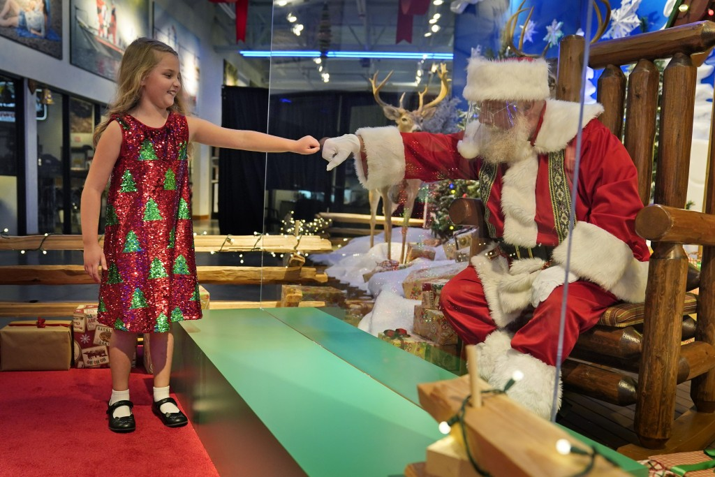 Sydney Poulos, 8, gives Santa a fist bump through a transparent barrier at a Bass Pro Shop in Bridgeport, Conn., Tuesday, Nov. 10, 2020. Santa Claus i...