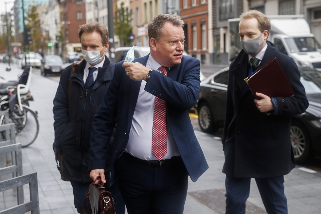 Britain's chief negotiator David Frost, center, removes his face mask to talk to the media as he arrives for Brexit talks with EU chief negotiator Mic...