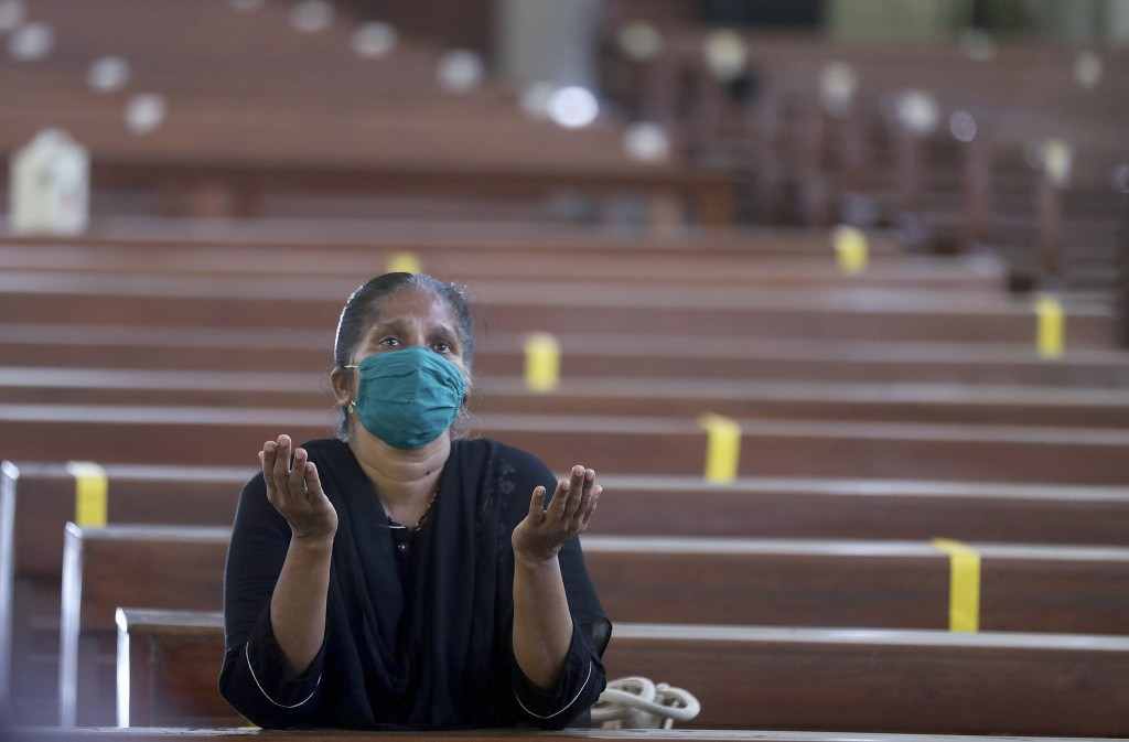 A Christian devotee wearing a mask offers prayers at a Church in Mumbai, India, Monday, Nov. 16, 2020. Religious places across the Maharashtra state r...