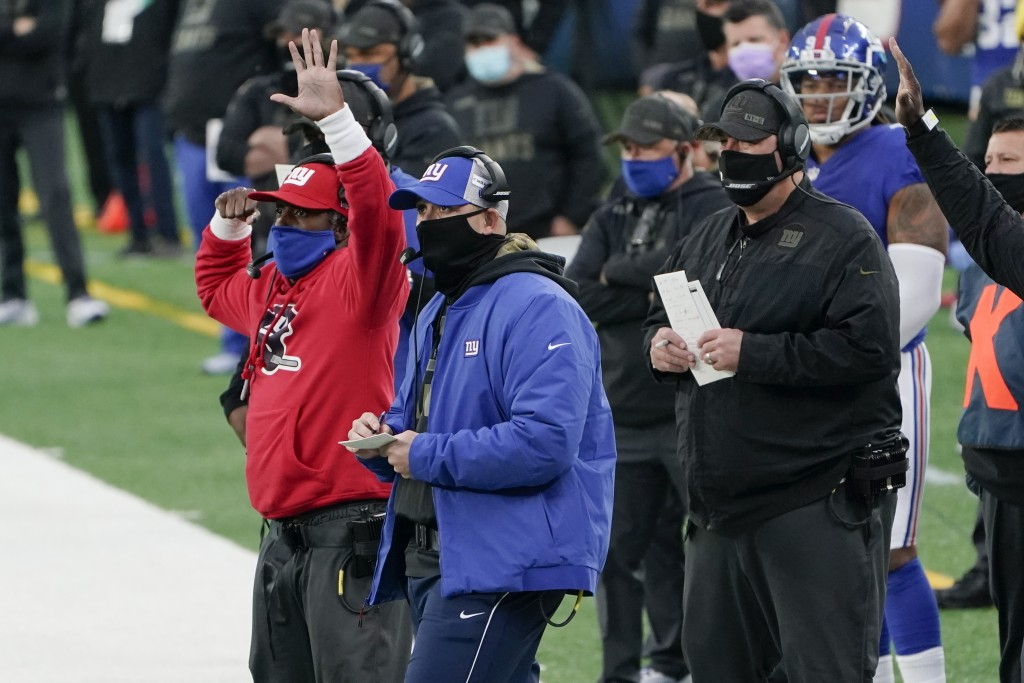 New York Giants head coach Joe Judge, center, watches his team during the second half of an NFL football game against the Philadelphia Eagles, Sunday,...