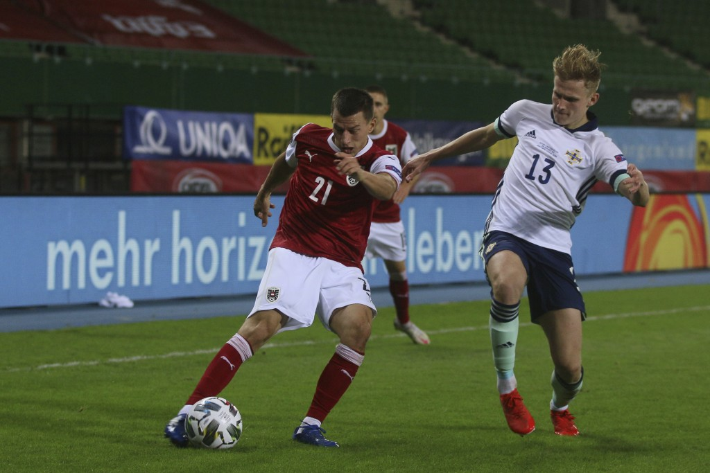 Austria's Stefan Lainer, left, is challenged by Northern Ireland's Alistair Edward McCann during the UEFA Nations League soccer match between Austria ...