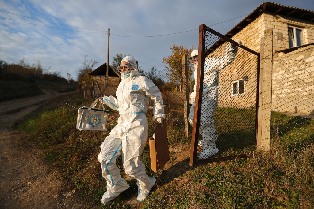 Election officials wearing biohazard suits, for protection against the COVID-19 infection, carry a mobile ballot box while visiting voters with mobili...